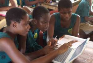 Children at Mawuli Basic School share a laptop