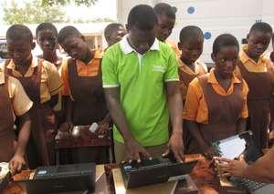 Pupils watch technicians configure the new laptops
