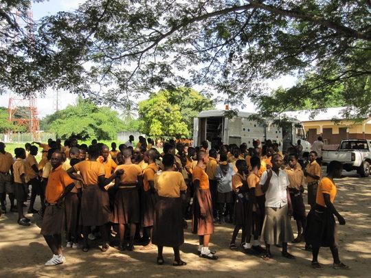 Excited children crowd around the library van.