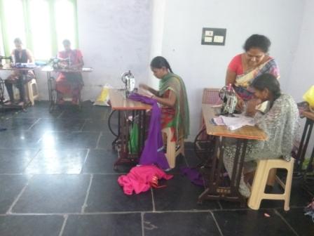 Girls are practicing cloths stitching on machine