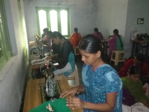 Trainees are practicing stitching cloths on machin