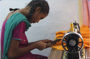 Adolescent girl stitching with the sewing machine