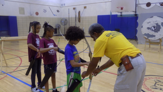 Campers learning archery with Coach Brown