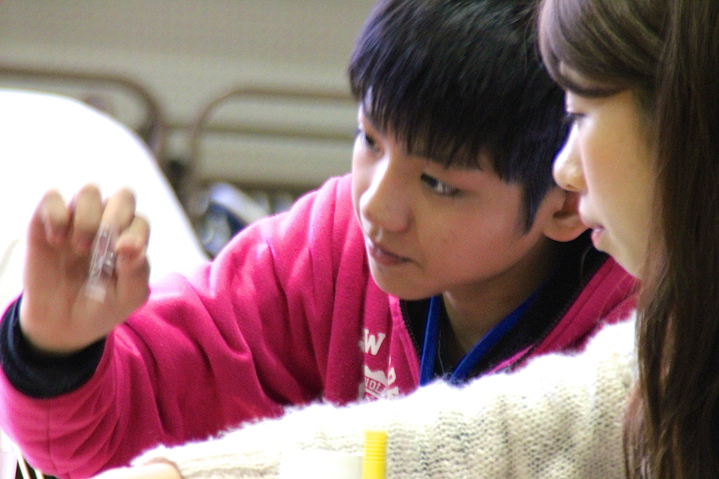 A boy is working together with a volunteer student