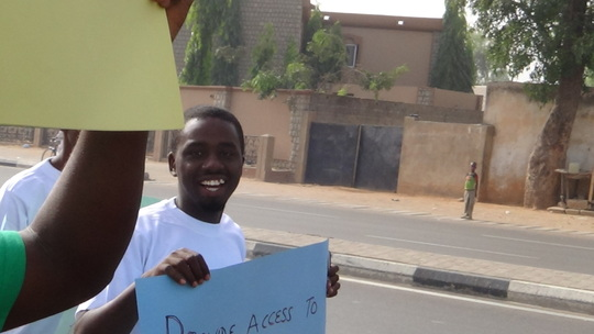 Aminu aka 'Pele' holding up a placard for water