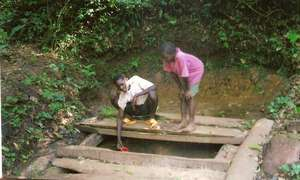 Children collect water from a pond improvised with