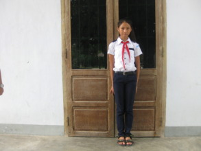 Nhi in front of her house.