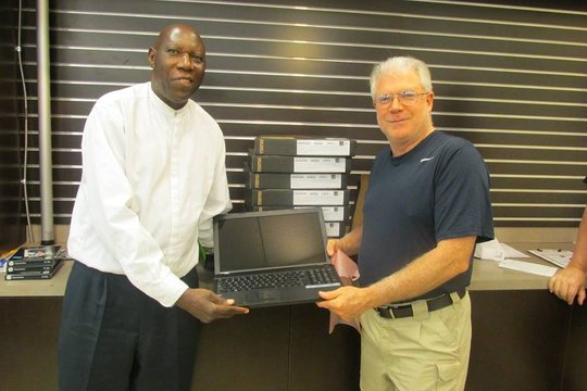 Receiving 10 laptops for the school from the donor