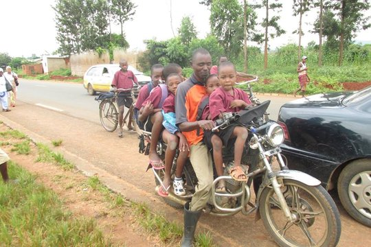 A motorcycle taxi transporting students