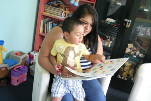 A mother reads a book to her son in the playroom.