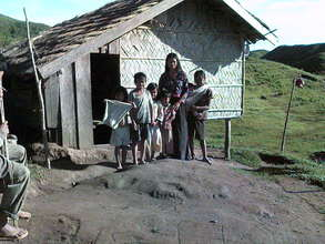 mother and children in front of their bamboo house