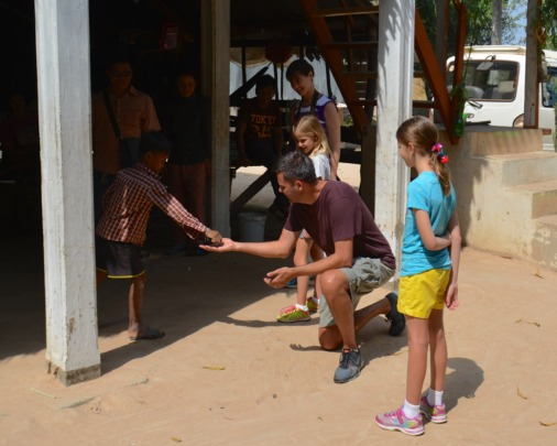 Thiessens encourage Cambodian boy to play marbles.
