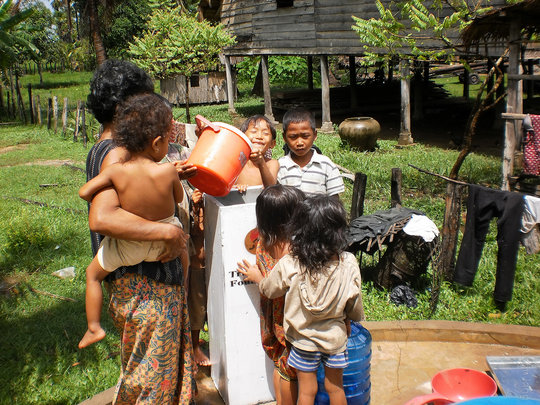 Mother using a bio-sand water filter for her child