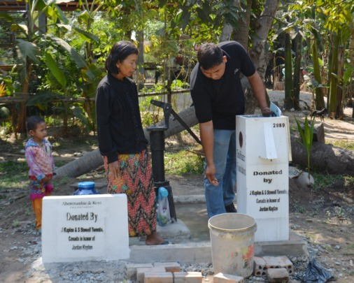 Staff explains use of a water filter to villager