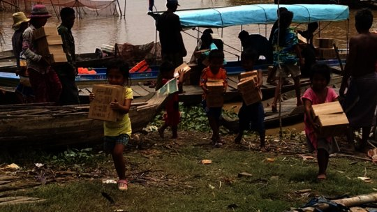 Children helping unload PUR water sachets