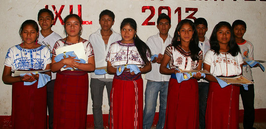 Graduating youth proudly hold their diplomas