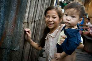 A loving sister babysits her brother in the slums
