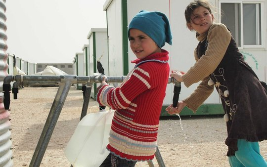 Girls collect water. Courtesy of OXFAM