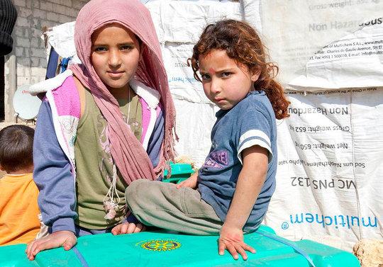 Refugee children with relief supplies
