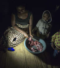 Annety cutting meat at night-time
