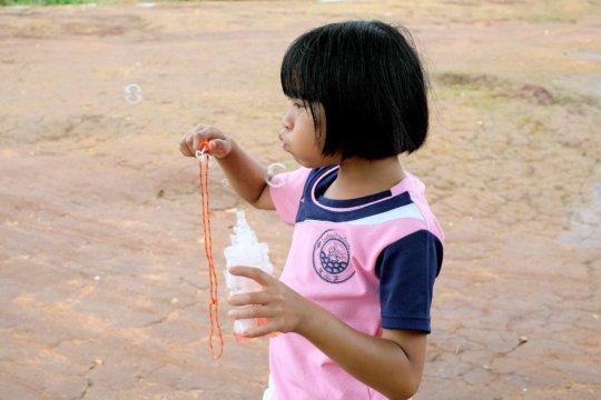 Blowing bubbles at Koung Jor refugee camp