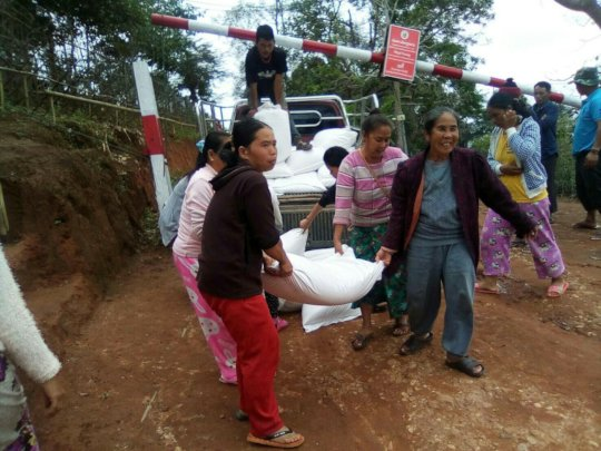Women help to carry rice sacks into the community