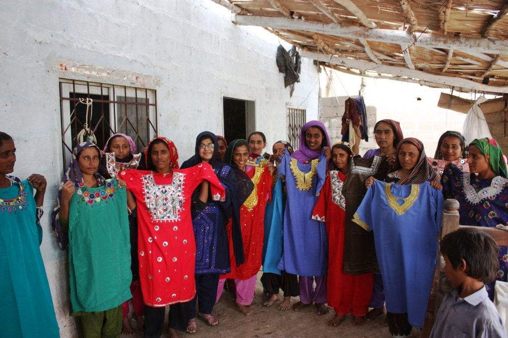 Khalida Brohi standing with women beneficiaries