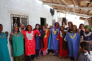Khalida Brohi standing with women beneficiaries