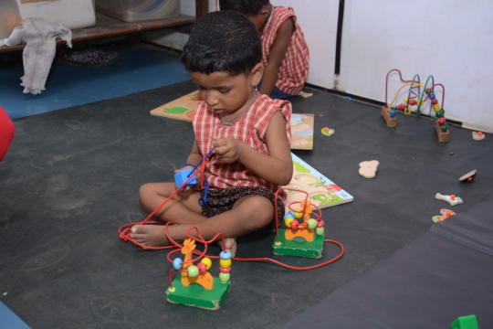 Child at our centre playing with beads stackers!
