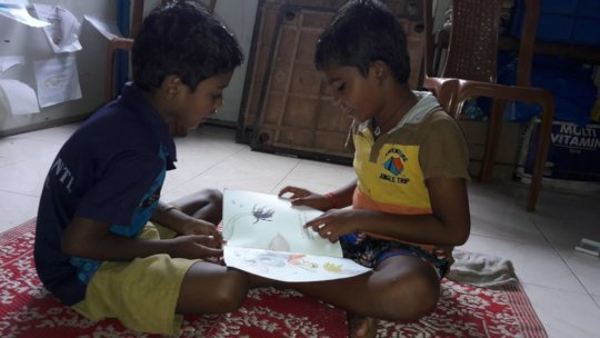 Child enjoying reading of storybook with a friend