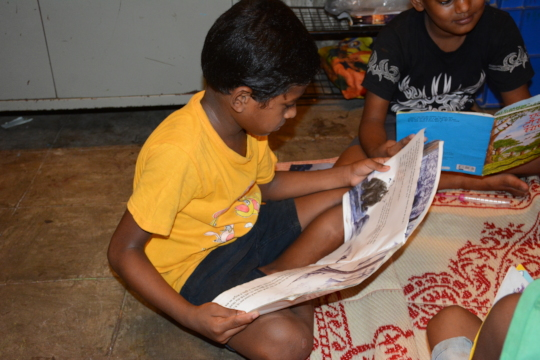A child from a centre trying to read the book