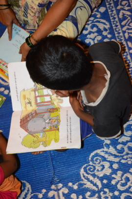 Child engrossed in reading at our centre