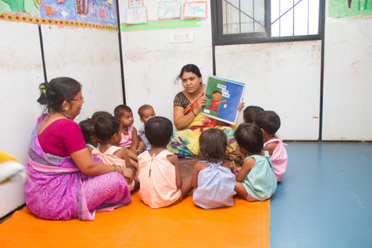 Teacher reading story to our creche section !