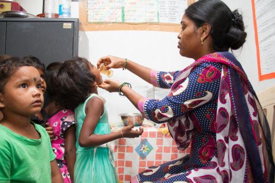 Teacher giving medicine to children