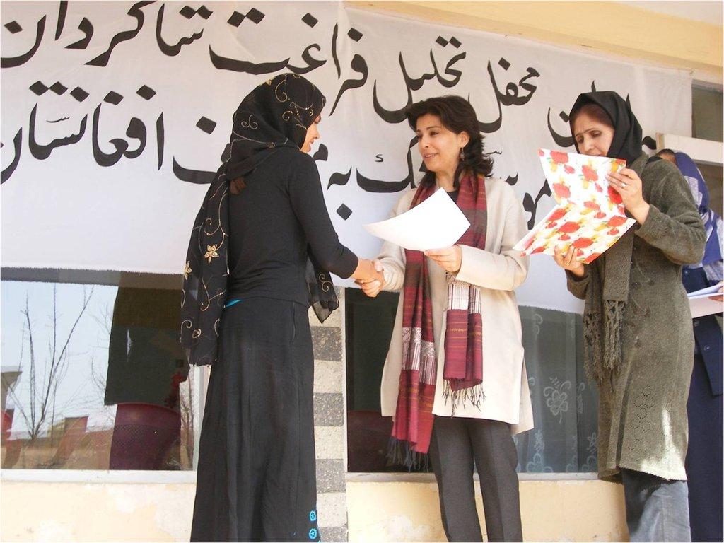 Hassina Sherjan issuing diplomas to graduates