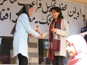 Hassina Sherjan in front of school