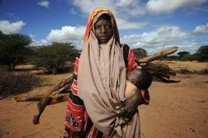 Woman Carrying Child & Firewood