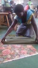 A woman making School Uniform at Amwonya