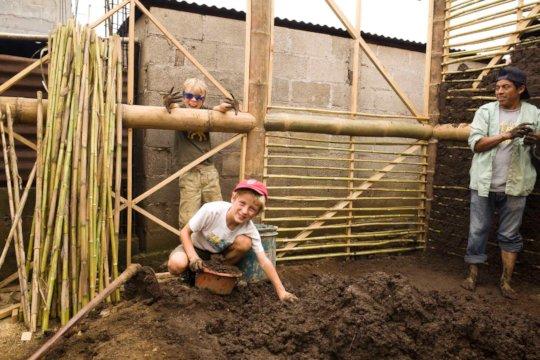 volunteers help with mud work on walls