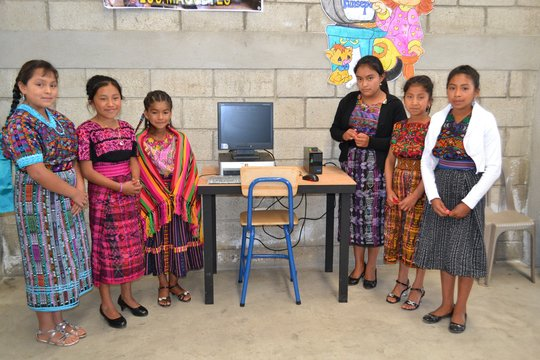 Girls proudly display a  school computer