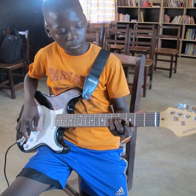 A young guitar student focused on his instrument