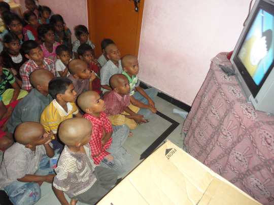 Orphan Children enjoying while watching the TV
