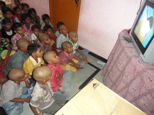 Orphan Children enjoying while watching the TV