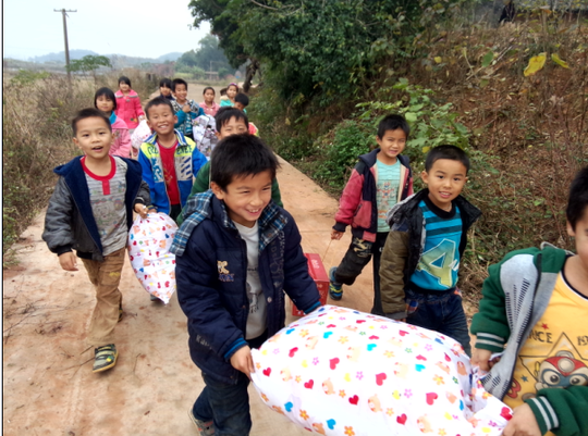 Children helping volunteers carry school supplies
