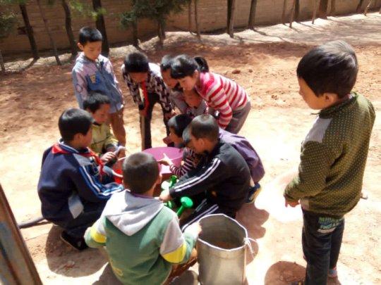 Children distributing water with buckets
