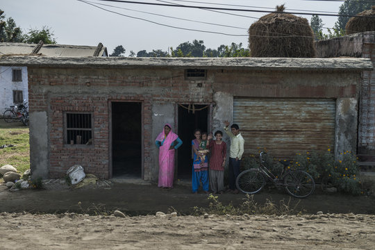 Manju and her family wave outside their home