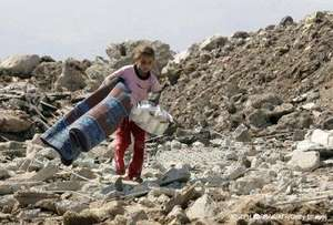 A girl walks over rubble with her belongings
