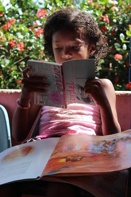 Girl enjoying reading at Ms. Edna's home