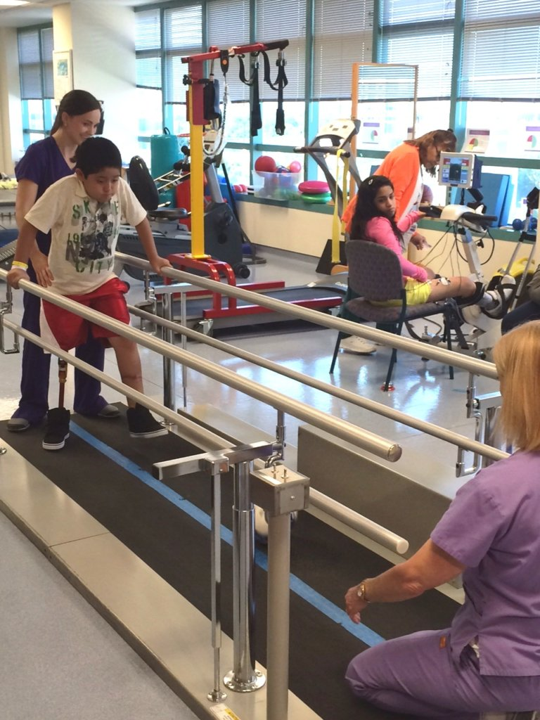 Brayan and physical therapist practice walking
