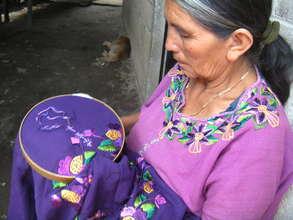 Dona Clara embroidering a blouse.